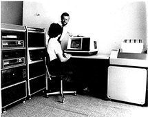 How things have changed – in 1975, a dark-haired Bill demonstrates the CDS software to a member of Pilot's Oil's staff.   The 'mini' computer had 32KB of memory while the large disks only held 5 megabytes of data collectively!