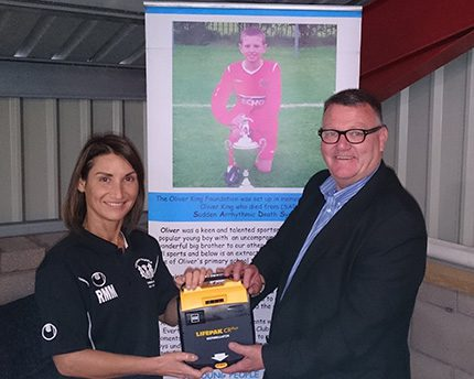 Brogan's Ros Murray hands over the defibrillator unit to Mark King