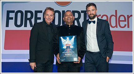 Holding the award for best oil company initiative SB Prasad, chief commercial officer, retail is flanked by awards host Brian Conley (l) and Blake Gladman, research and insight director for Him! which sponsored this award